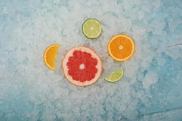 砕いた氷の背景の上に、新鮮なジューシーな柑橘系の果物のスライス、ピンクグレープフルーツ、オレンジと緑のライムをクローズアップ、高角度のビュー、真上