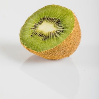 Close-up of fresh kiwi fruits on white surface