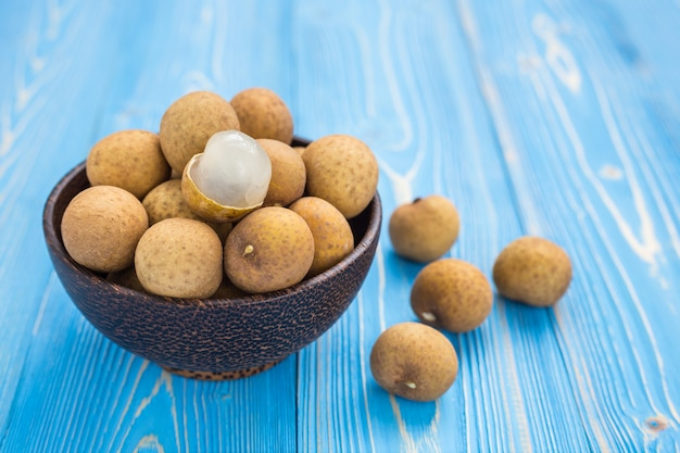 Close up fresh longan tropical fruit on blue wooden plank background