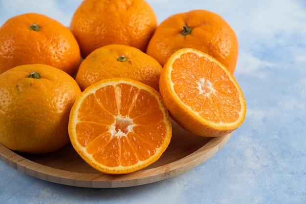 Primo piano di mandarini freschi sul piatto di legno