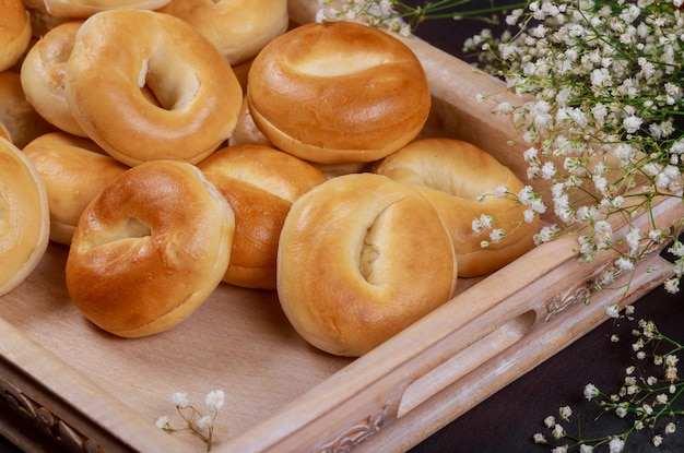 Close up of fresh mini bagels on wooden tray.