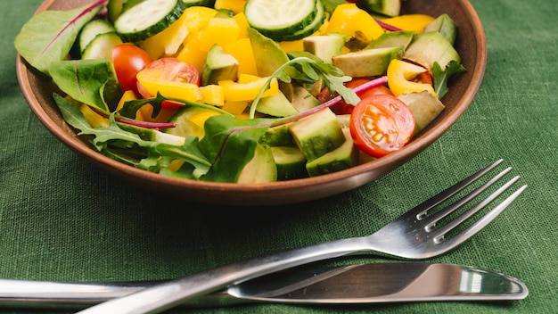 Close-up of fresh mixed vegetable salad and cutlery on green tablecloth