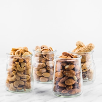 Close-up of fresh nut food in jar on marble surface