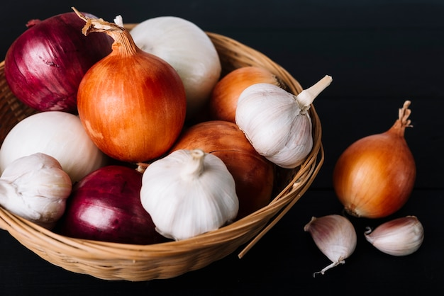 Close-up of fresh onions and garlic bulbs in basket on black background