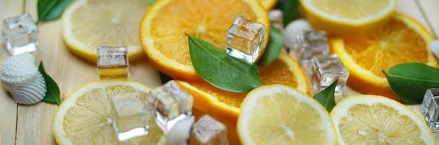 Close up of fresh orange lemon sea shells leaves cube ice summer background banner