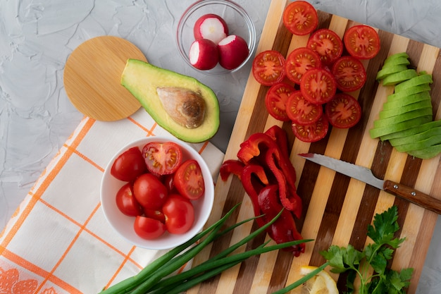 Close up fresh organic flat lay sliced vegetables on the cutting board, tomato, avocado, peppers