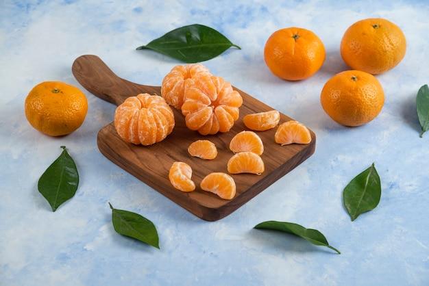 Primo piano di mandarini biologici freschi. intero o pelato su tavola di legno