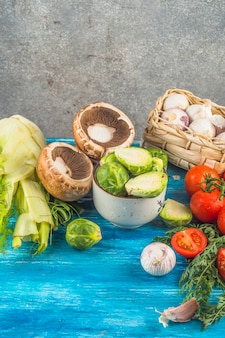 Close-up of fresh organic vegetables on blue wooden surface