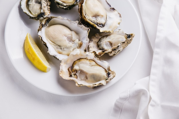 Close up of fresh oysters served in white plate with sliced of lemon on white tablecloth.