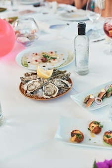 Close-up of fresh oysters with lemon on the restaurant table.