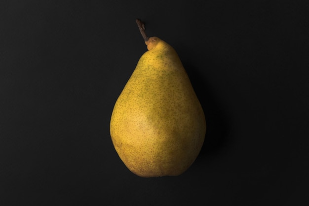 Close up of a fresh pear isolated over black