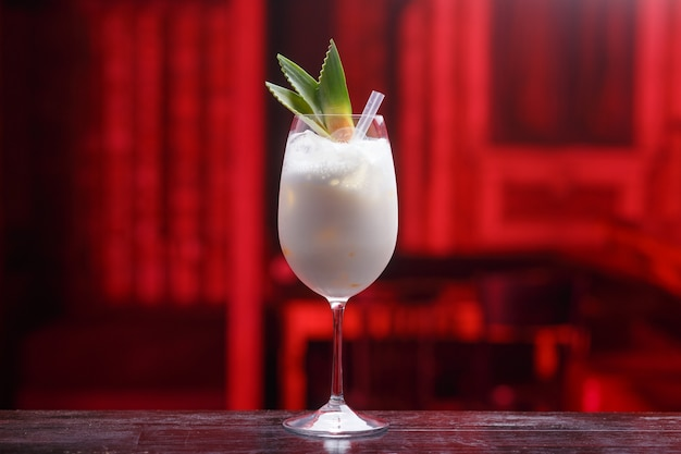 Close up of a fresh pina colada cocktail with coconut milk and banana on the wooden counter, isolated on a bar, red blurred light space. copy space.