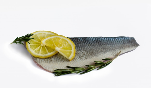 Close-up of fresh raw sea bass fish fillet with rosemary and pieces of the lemons