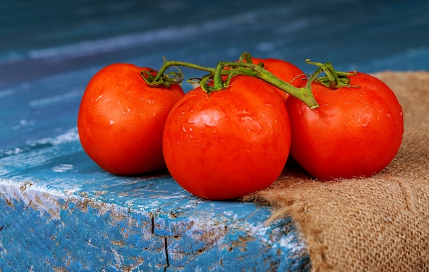 Close-up of fresh ripe tomatoes on wooden board blue