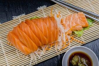Close up fresh salmon sashimi set salad on bamboo plate, Japanese food.