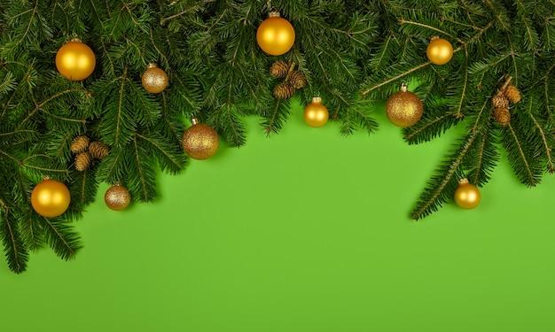 복사 공간이 있는 녹색 배경 위에 원뿔, 황금색 공, 싸구려로 장식된 신선한 가문비나무 또는 소나무 크리스마스 나무 가지를 닫습니다
