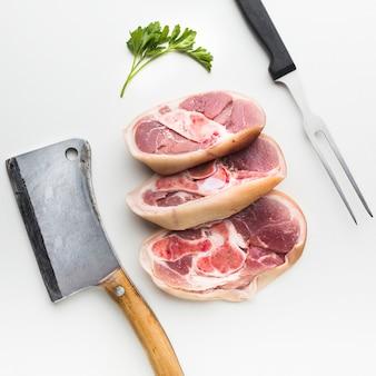 Крупным планом свежие стейки с ножом на столе