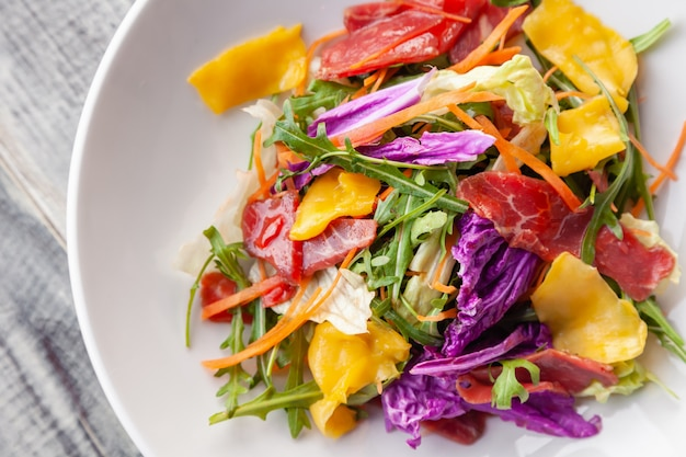 Close-up fresh summer salad with bresaola meat, greens, arugula, mango, carrot, chinese cabbage.