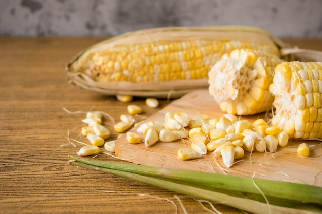 Close up of fresh sweet corn on wooden table.