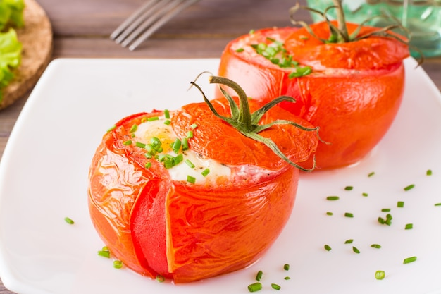 Close-up of fresh tomatoes baked with cheese and egg sprinkled with green onions on a plate on a wooden table