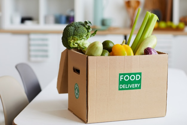 Close-up of fresh vegetables in cardboard box on the table delivered to home