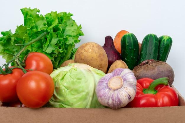 白い背景の上の段ボール箱に新鮮な野菜を閉じる