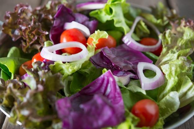 Close up di insalata di verdure fresche nella ciotola con rustico vecchio sfondo in legno. concetto di cibo sano.