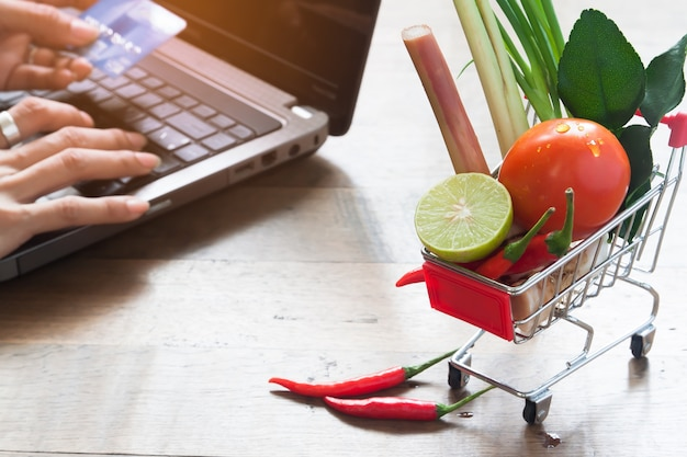 Close up of fresh vegetables in shopping cart with woman using laptop and credit card, online shopping