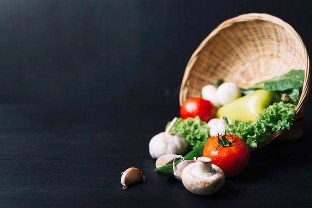 Close-up of fresh vegetables with wicker basket on black wooden backdrop