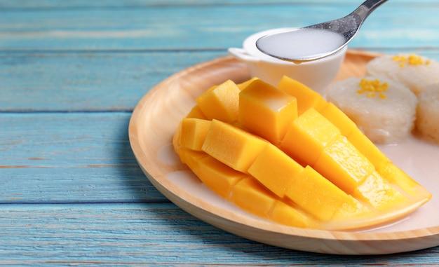 Закройте вверх по свежей желтой кожуре манго и нарезанным кубиками с липким рисом.