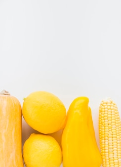 Close-up of fresh yellow vegetables on white background