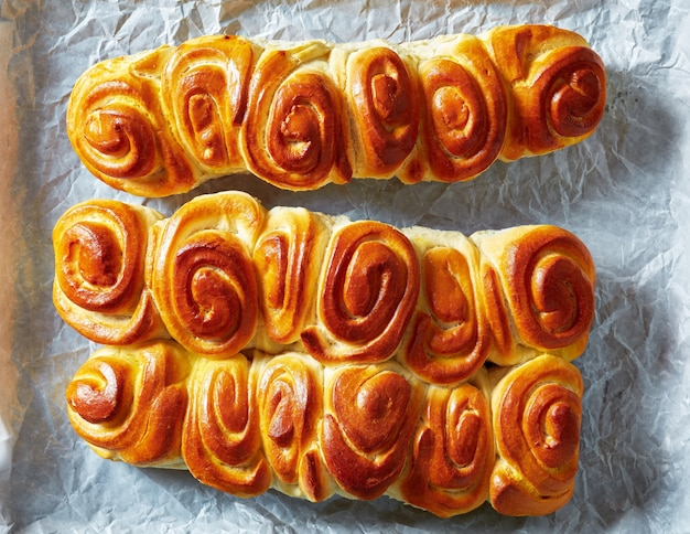 Close-up of freshly baked hot pull apart rolls, homemade yeast dinner buns on a paper, horizontal view from above, flatlay, close-up