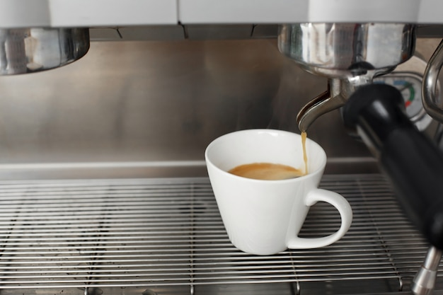 Close-up of freshly brewed coffee is poured from a coffee machine into a white cup