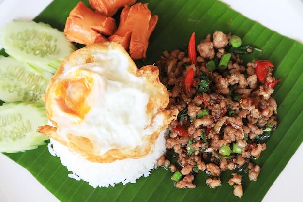 바나나 잎과 흰 접시에 넣어 쌀과 튀긴 계란과 튀긴 바질 칠리 돼지 고기를 닫습니다
