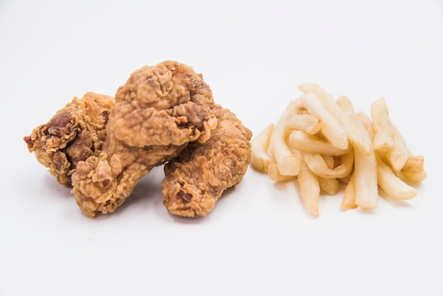 Close-up of fried chicken drumstick with french fries on white backdrop