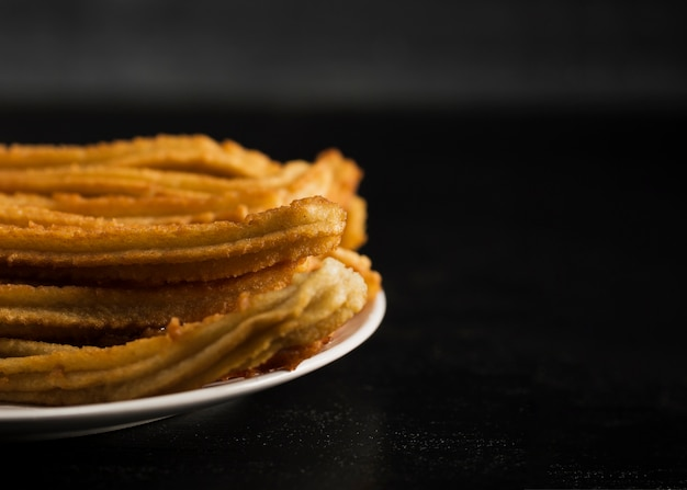Close-up fried churros with sugar and copy space