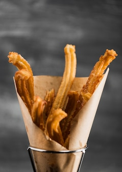 Close-up fried churros in a wrapping paper