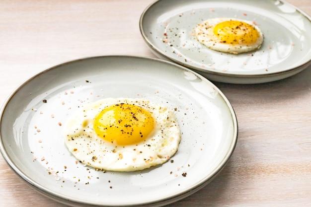 白い木製のテーブルにコショウとプレートで2つの目玉焼きのクローズアップ。朝の朝食のコンセプト。閉じる。セレクティブフォーカス。コピースペース