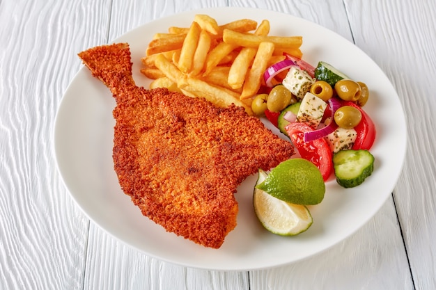Close-up fried flounder in breadcrumbs served with fresh vegetables, feta, olives greek salad and french fries on a white plate on a wooden table, view from above