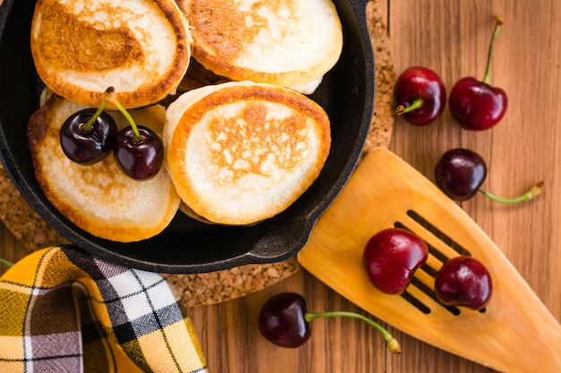 Close-up of fried pancakes in a iron pan and ripe cherries on a wooden table. top view