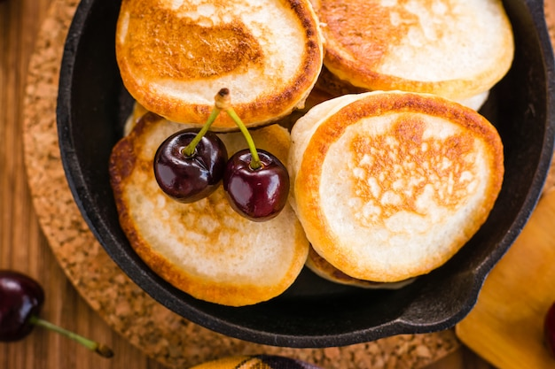 Close-up of fried pancakes in a iron pan and ripe cherries