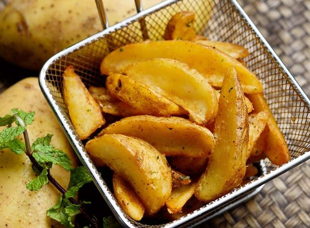 Закройте жареные дольки картофеля или картофель в металлической корзине