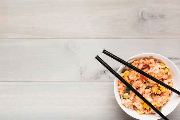 Close-up of fried rice bowl with black chopsticks on table