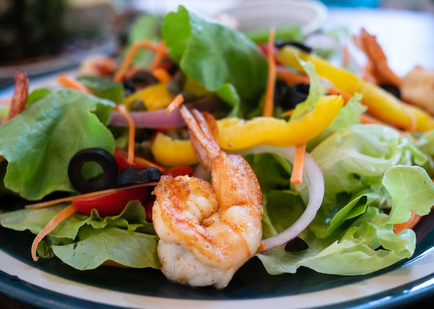 Close up fried shrimp in delicious salad with vegetables.