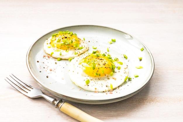 プレートソルト、コショウ、ネギ、フォークで卵2個をクローズアップで揚げた。朝の朝食のコンセプト。閉じる。セレクティブフォーカス。コピースペース