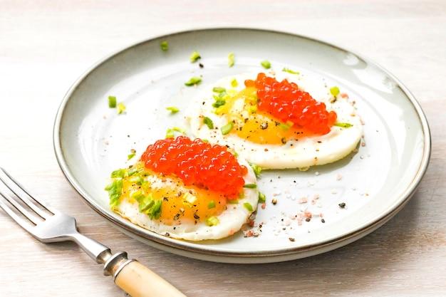 クローズアップで揚げた卵2個、赤キャビア、調味料を皿に盛り付けました。朝の朝食のコンセプト。閉じる。セレクティブフォーカス。コピースペース