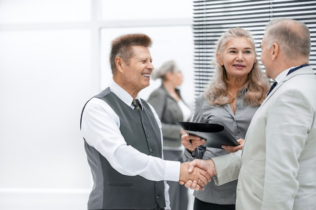 Close up. friendly business people shaking hands with each other. the concept of cooperation