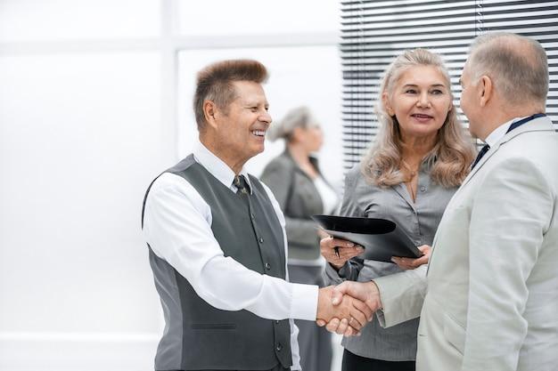 閉じる。お互いに握手するフレンドリーなビジネスマン。協力の概念