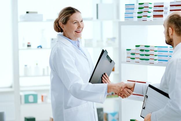閉じる。新入社員と握手するフレンドリーな女性薬剤師。
