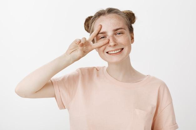 Primo piano dell'adolescente felice sorridente amichevole della testarossa che mostra il gesto di pace